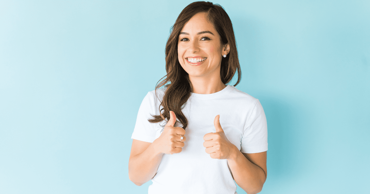 Woman-Giving-Thumbs-Up-Over-Plain-Background